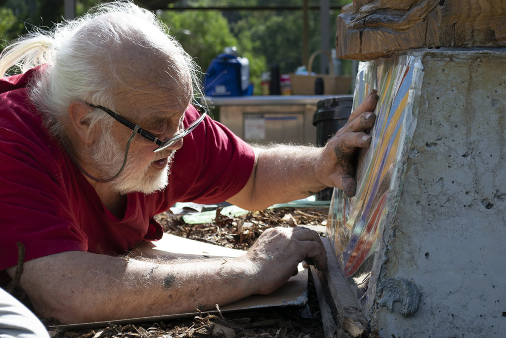 Local artist Franc Smith placing mosaics on the sculpture base
